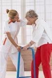 Sjuksköterska Assisting Senior Woman som går med Zimmer arkivfoto