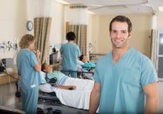 Sjuksköterska With Colleagues i sjukhuset PACU Royaltyfri Bild