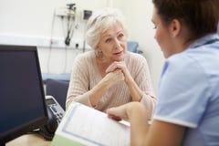 Sjuksköterska Discussing Test Results med patienten fotografering för bildbyråer
