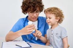 Sjuksköterska Giving Vitamins till det lilla barnet royaltyfria bilder