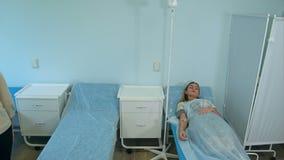 Sjuksköterska i handskar och maskering som sätter kvinnliga patienter på en droppande i en sjukhussal arkivfilmer