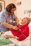 Sjuksköterska i Läkarundersökning-kirurgisk omsorgenhet Arkivbild
