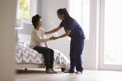 Sjuksköterska Making Home Visit till den höga kvinnan arkivfoto