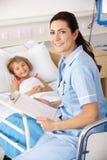 Sjuksköterska med barnet i UK-sjukhus Fotografering för Bildbyråer