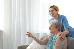 Sjuksköterska med den äldre kvinnan, utrymme för text Hjälpa högt folk royaltyfri fotografi