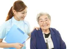 Sjuksköterska med den gamla kvinnan Arkivbild