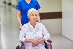 Sjuksköterska med den höga kvinnan i rullstol på sjukhuset Royaltyfria Bilder