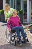 Sjuksköterska med den höga kvinnan i rullstol utomhus arkivbild
