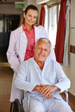Sjuksköterska med den höga manen i rullstol Arkivfoto
