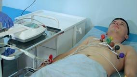 Sjuksköterska med provet för kardiogram för ECG-utrustningdanande till den manliga patienten i sjukhusklinik stock video