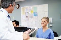 Sjuksköterska At Nurses Station för doktor In Discussion With royaltyfri fotografi
