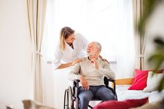 Sjuksköterska och hög man i rullstol under hem- besök Arkivbild