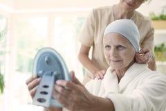 Sjuksköterska och patient med den bärande sjaletten för cancer och se spegeln arkivfoto