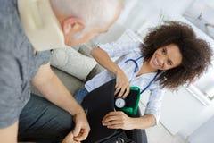 Sjuksköterska på för blodtryckprovning för hem- besök packande bort utrustning royaltyfri foto