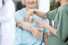 Sjuksköterska Putting Crepe Bandage på patients hand på Rehabmitten Royaltyfri Bild