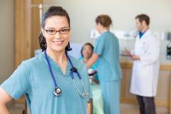 Sjuksköterska Smiling Against Patient och läkarundersökning Team In Royaltyfri Foto