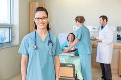 Sjuksköterska Smiling With Patient och läkarundersökning Team In royaltyfri foto