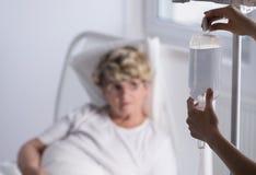 Sjuksköterska som ändrar en droppandepåse Royaltyfria Foton