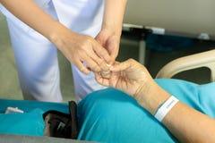 Sjuksköterska som använder bomullstoppet som blöder från blodprov från ett finger fotografering för bildbyråer