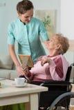Sjuksköterska som att bry sig om handikappad kvinna Arkivbild