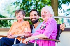 Sjuksköterska som dricker kaffe med pensionärer på terrass Royaltyfri Bild