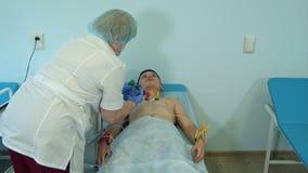 Sjuksköterska som fäster elektrodblock till den tålmodiga bröstkorgen för ` s arkivfilmer