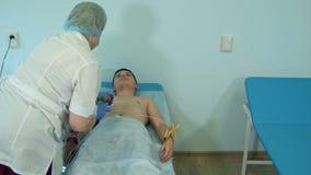 Sjuksköterska som förbereder den tålmodiga bröstkorgen för ` s för att fästa elektrodblock för ECG lager videofilmer