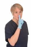Sjuksköterska som göra en gest för tystnad Arkivbild