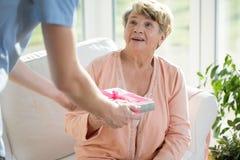 Sjuksköterska som ger en gåva Royaltyfria Foton