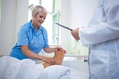 Sjuksköterska som ger fotbehandling till patienten arkivfoton