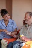 Sjuksköterska som ger läkarbehandlingen till den höga mannen Royaltyfri Fotografi