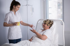 Sjuksköterska som ger medicin till patienten Royaltyfri Bild