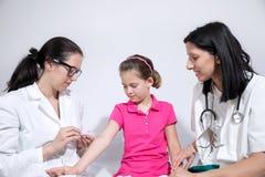 Sjuksköterska som ger vaccineringinjektionen till liten flickatålmodign Royaltyfri Foto