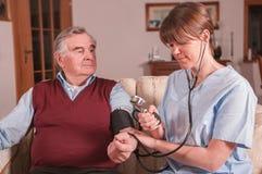Sjuksköterska som hemma tar blodtryck royaltyfri foto