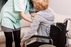 Sjuksköterska som hjälper den rörelsehindrade kvinnan Royaltyfria Bilder