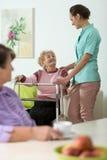 Sjuksköterska som hjälper den rörelsehindrade kvinnan Royaltyfria Foton