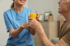Sjuksköterska som inomhus ger exponeringsglas av fruktsaft till den äldre mannen Hjälpa högt folk royaltyfri foto