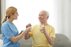 Sjuksköterska som inomhus ger läkarbehandlingen till den äldre mannen arkivbild
