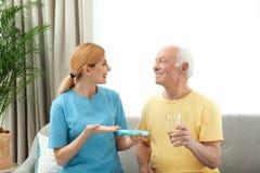 Sjuksköterska som inomhus ger läkarbehandlingen till den äldre mannen royaltyfri fotografi