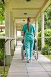 Sjuksköterska som kör rullstolen Arkivbild