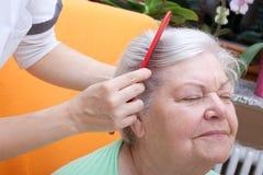 Sjuksköterska som kammar pensionären till och med henne hår Royaltyfri Fotografi
