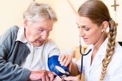 Sjuksköterska som mäter blodtryck på den höga patienten Royaltyfri Fotografi