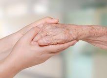 Sjuksköterska som rymmer den gamla tålmodiga handen royaltyfri foto