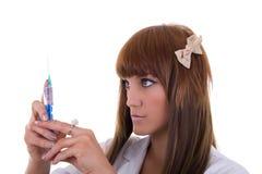 Sjuksköterska som rymmer en visare och en injektionsspruta Royaltyfria Bilder