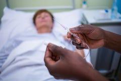 Sjuksköterska som rymmer iv-droppande Arkivfoto