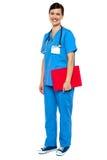 Sjuksköterska som slitage den blåa uniform holdingredclipboarden arkivbilder