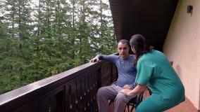 Sjuksköterska som spenderar tid med den ledsna unga mannen i rullstol arkivfilmer