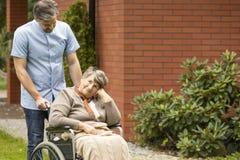 Sjuksköterska som stöttar den rörelsehindrade höga kvinnan i rullstolen fotografering för bildbyråer