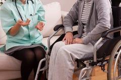 Sjuksköterska som talar med den rörelsehindrade patienten royaltyfri fotografi