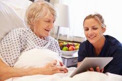 Sjuksköterska som talar till hög kvinnlig tålmodig i sjukhussäng arkivbilder